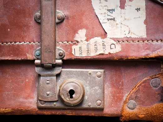 Detail of old brown leather suitcase with torn labels : Stock Photo
