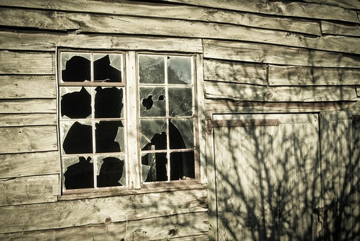 Broken window panes on wooden outbuilding : Stock Photo