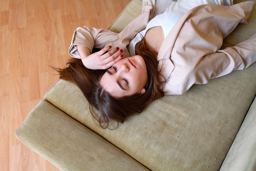 Stock Photo: 1566-806664 Portrait of a young blond woman lying on sofa