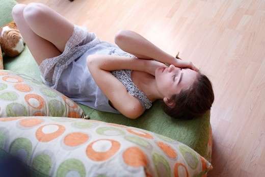 Stock Photo: 1566-806708 Portrait of a young blond woman lying on sofa
