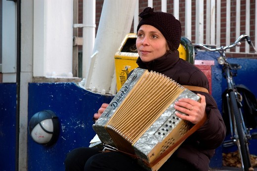 A young Roumenian woman plays the accordion in the streets of Utrecht. : Stock Photo