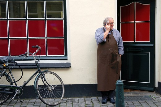 Man in apron making a phone call outside his shop. : Stock Photo