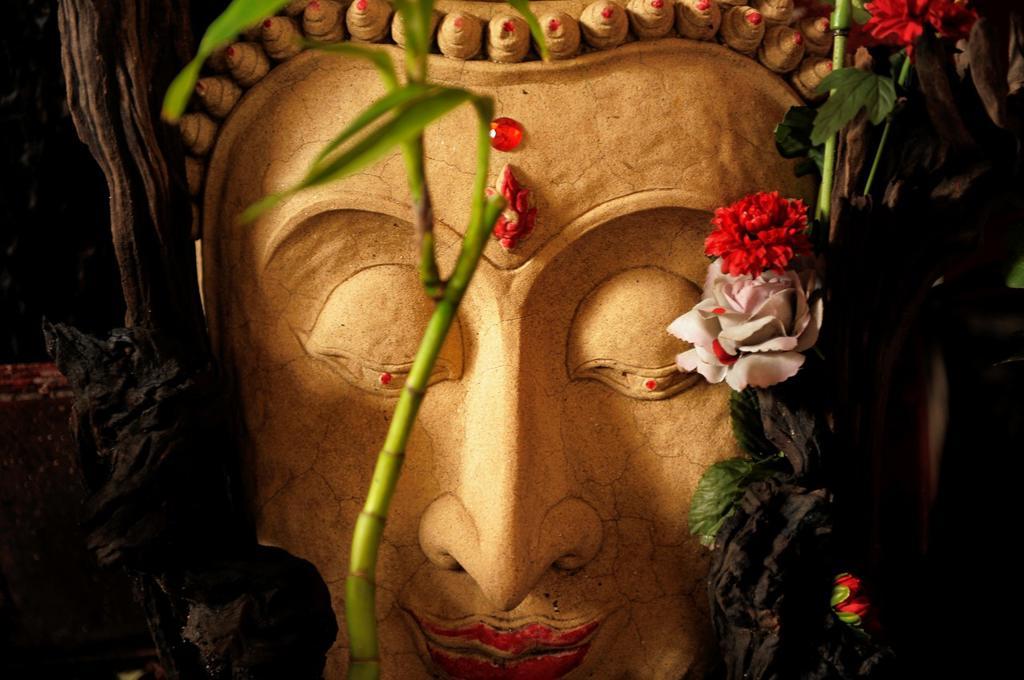 buddha stone image decorated with flowers , chinatown , bangkok, thailand : Stock Photo