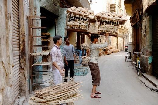 Stock Photo: 1566-810480 delivery boy with stacks of egyptian bread eesh baladi , balanced on his head , islamic cairo , backstreet life , cairo , Egypt