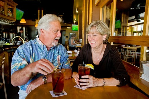 A happy middle aged married couple enjoy iced tea together in a Long Beach, CA, restaurant : Stock Photo