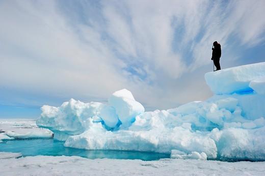 Inuit guide observing melting ice, Floe edge, Arctic Bay, Baffin Island, Nunavut, Canada : Stock Photo