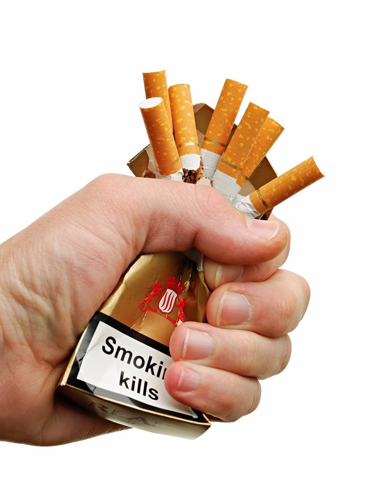 Hand Crushing a Packet of Cigarettes, Close Up, Cut Out : Stock Photo