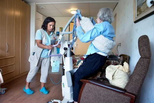 A professional nurse of a Rotterdam nursing home helping an elderly inhabitant from her chair, using a lifter. : Stock Photo