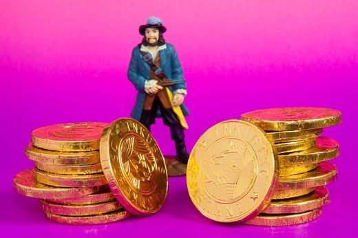 Stock Photo: 1566-826076 Chokolate golden coins with miniature plastic doll