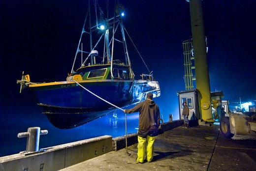 Commercial fishing boat being hoisted out of Pacific Ocean in Port Orford, Oregon, all boats are stored on pier, not moored in water : Stock Photo