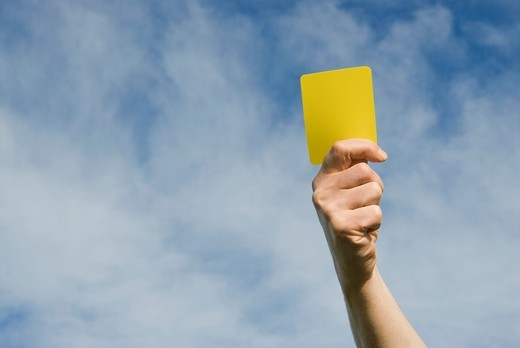 Stock Photo: 1566-832376 Hand of referee waving a yellow card