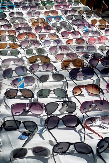 An assortment of sunglasses for sale at an outdoor market : Stock Photo