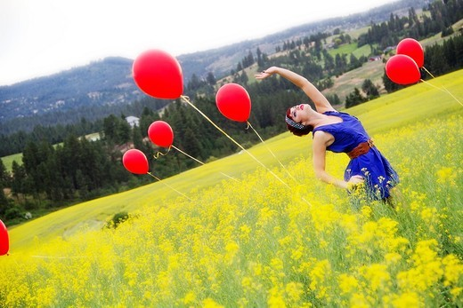 A beautiful young caucasian female in a canola field with balloons near Spokane, Washington, USA. : Stock Photo