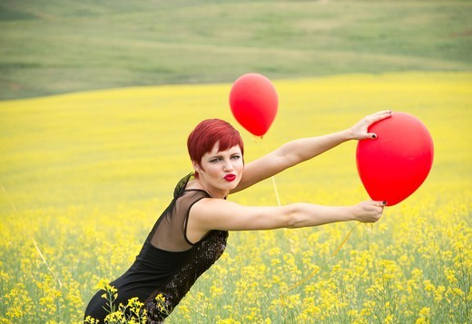 Stock Photo: 1566-833894 A beautiful young caucasian female in a canola field with balloons near Spokane, Washington, USA.