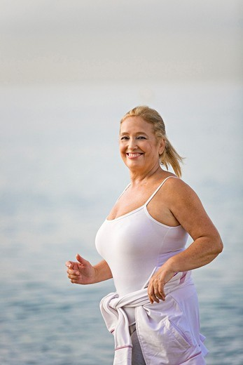 Portrait of a senior adult woman running at the beach : Stock Photo