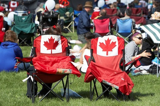 people sitting in maple leaf chairs in the crowd at festival on canada day Saskatoon Saskatchewan Canada : Stock Photo