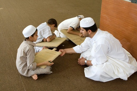 Zliten, Libya  Boys Write Verses from the Koran on their Prayer Boards in the Madrasa of Sidi Abdusalaam  Their teacher, or muqri, supervises  He wears the traditional white garment, a juba, and a traditional hat, a tagiyah : Stock Photo