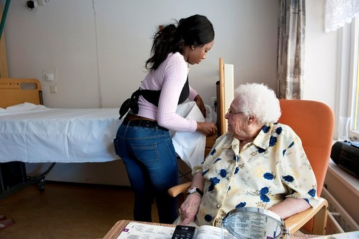 Stock Photo: 1566-836408 Young intern making up the bed of an elderly inhabitant, after helping her getting dressed.