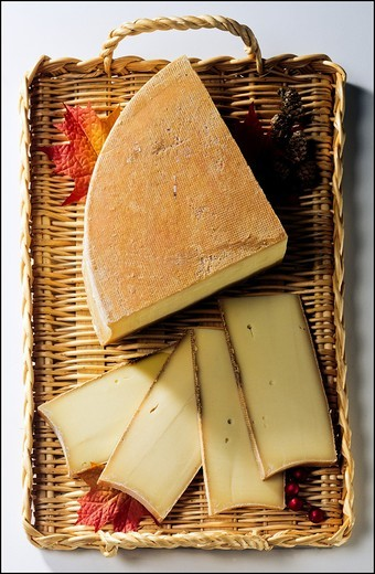 Abondance de Savoie French cheese and slices on wicker tray : Stock Photo