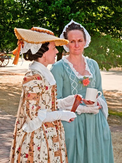Actresses dress in historic clothing on the streets of Colonial Williamsburg, VA, a ´living history´ museum with an assemblage of buildings populated with historical reenactors who work, dress, and talk as in colonial times : Stock Photo