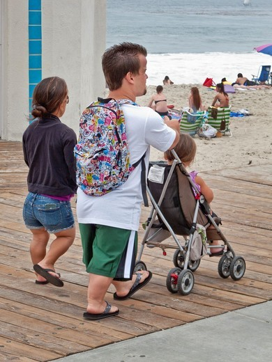 Midget parents push their normal size daughter in a stroller at Laguna Beach, CA : Stock Photo