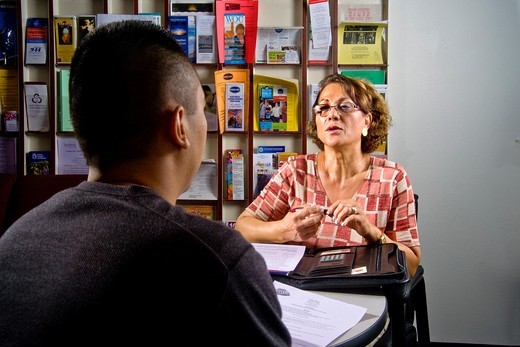 Stock Photo: 1566-840849 An Iranian-American counselor talks with a Hispanic male student at Saddleback Community College in Mission Viejo, CA  Note career brochures on wall