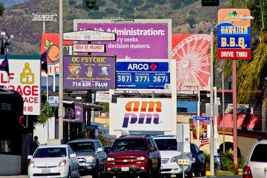 Afternoon traffic passes retail advertising signs in Orange, CA : Stock Photo