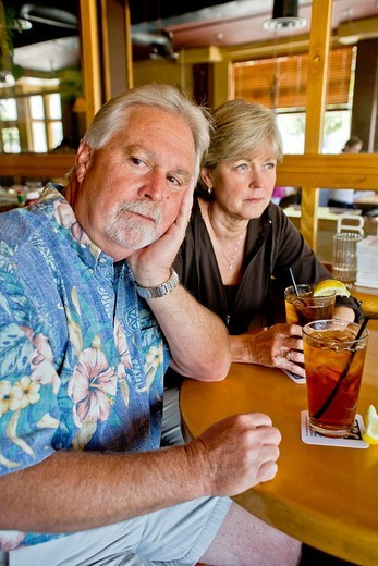 A middle aged couple appeared indifferent to each others´ company over iced tea together in a Long Beach, CA, restaurant : Stock Photo