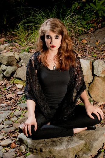 A 19 year old brunette woman with dramaitc make up looking directly at the camera sitting cross legged on rocks in a garden. : Stock Photo