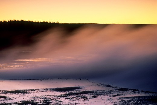 Steam from thermal hot spring rises at sunset, Fountain Paint Pot area, Yellowstone National Park, Wyoming : Stock Photo