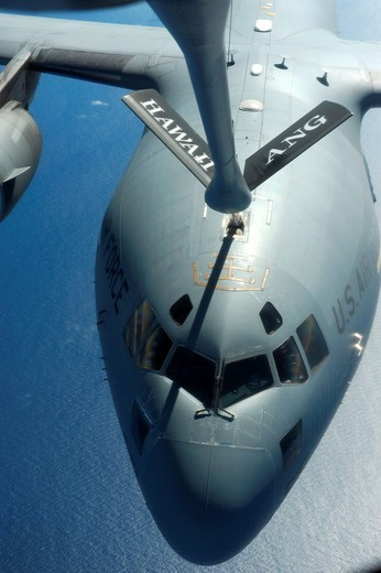 A C-17 Globemaster III takes on fuel from a KC-135 Stratotanker Sept  18, 2010, over the Pacific Ocean during a Total Force partnership mission to Andersen Air Base, Guam  The C-17 is assigned to the 15th Wing at Joint Base Pearl Harbor-Hickam, Hawaii, an. A C-17 Globemaster III takes on fuel from a KC-135 Stratotanker Sept  18, 2010, over the Pacific Ocean during a Total Force partnership mission to Andersen Air Base, Guam  The C-17 is assigned to the 15th Wing at Joint Base Pearl Harbor-Hickam : Stock Photo
