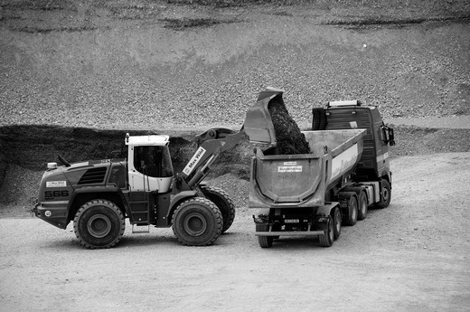 Excavator loading a truck in a gravel pit : Stock Photo