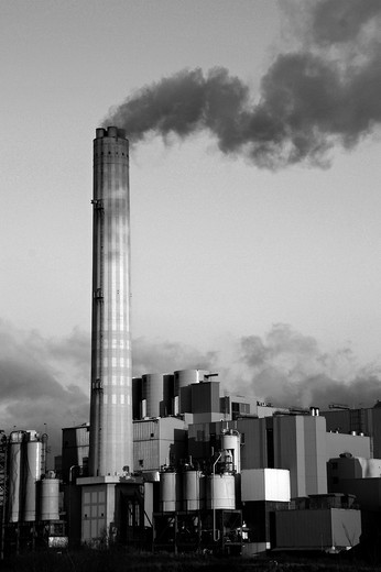 Smoke rises from the chimney of a factory : Stock Photo