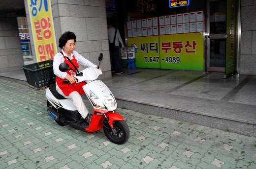Busan (South Korea): a woman driving a scooter on the sidewalk in Nam-gu neighborhood : Stock Photo