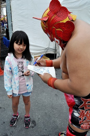 Naha (Japan): a wrestler giving an autograph to a young girl at the Dragon Boat Festival : Stock Photo