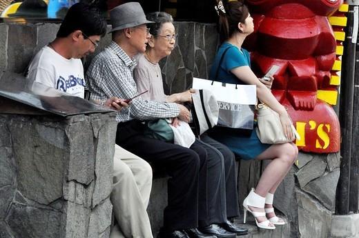 Naha (Japan): people waiting for a bus along Kokusai-dori : Stock Photo