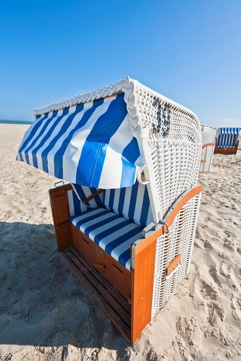 Single white wicker beach chair on the beach on the east frisian island of Spiekeroog, Lower Saxony, Germany, Europe : Stock Photo