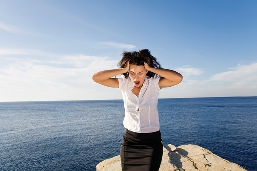 Stressed woman in a cliff by the sea : Stock Photo