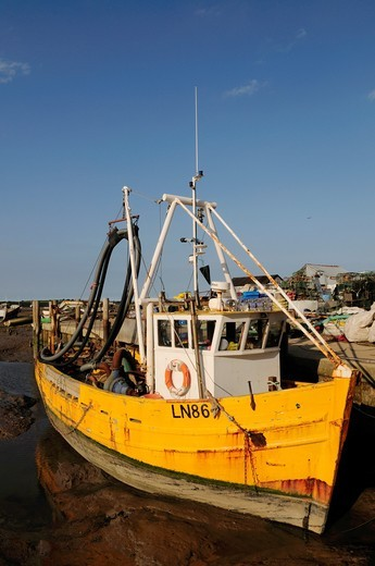 Yellow Fishing Boat at The Fisherman´s Quay at Brancaster Staithe, Norfolk, England, UK : Stock Photo