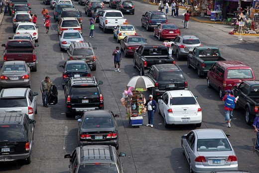 Tijuana, Mexico - As cars wait in long lines to cross the U S -Mexico border into California, vendors try to sell their wares : Stock Photo
