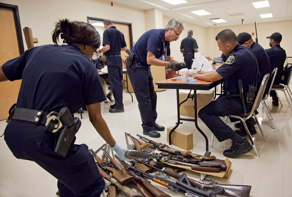 Stock Photo: 1566-849207 Detroit, Michigan - Police officers examine weapons turned in by residents in a gun buyback program  People were paid $25 to $200, depending on the type and quantity of weapons turned in