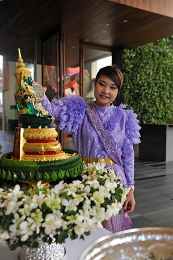 young woman pouring water over a statuette of Buddha Hansar hotel Bangkok, Thailand, Asia : Stock Photo