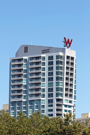 The W Hotel rising above the treetops of a waterfront park in Hoboken, New Jersey  The hotel offers views of the New York City Skyline directly opposite on the Hudson River  Hoboken, New Jersey, USA : Stock Photo