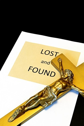 A Crucufix next to a Lost and Found sign  Conceptual image regarding faith : Stock Photo
