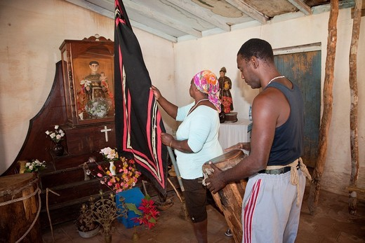 Stock Photo: 1566-855630 Cuba, Trinidad  Woman Raising Flag in front of Shrine to Saint Anthony San Antonio while Performing an Afro-Cuban Religious Ceremony