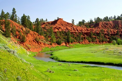 A small river runs through a colorful valley in Wyoming : Stock Photo
