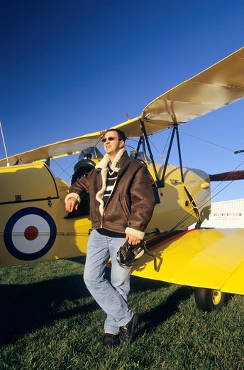 Pilot with flying jacket near old British trainer biplane De Havilland DH 82c Tiger Moth : Stock Photo