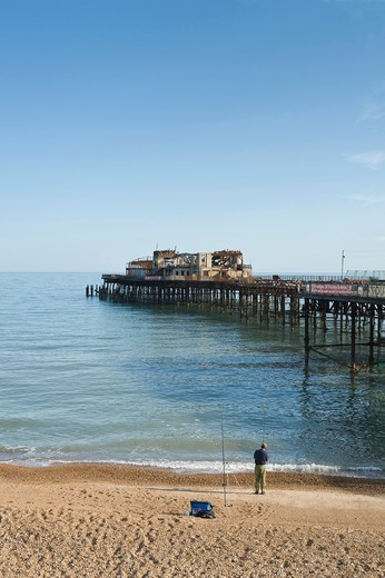 Man fishing on the beach by the pier, Hastings, East Sussex, England, UK : Stock Photo