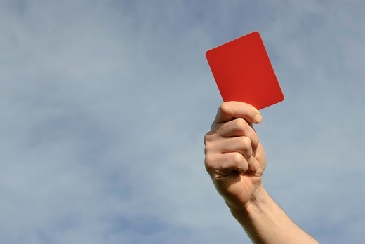 Hand of referee waving red card : Stock Photo
