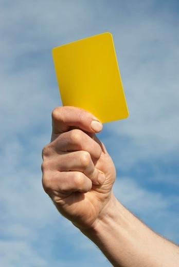 Referee waving yellow card : Stock Photo